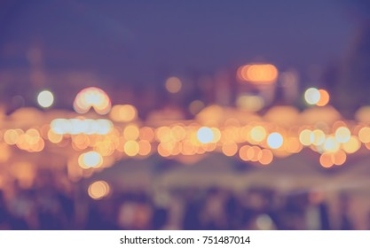 vintage tone blur image of people in night festival on street with bokeh for background usage .