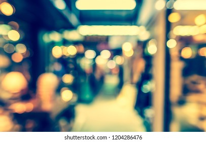vintage tone blur image of shopping mall with bokeh lights.