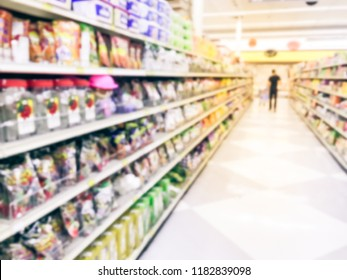Vintage tone blurred abstract customer shopping for cookies, candies, snacks, preserved fruits at Asian grocery store in US. Defocused snack time treats aisle on display with price tags at supermarket