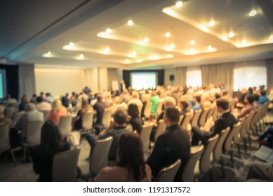 Vintage tone blurred business seminar meeting with LED projector screen, speaker speech on stage. Defocused rear view audience in conference hall room, listening talk show. Education, business concept