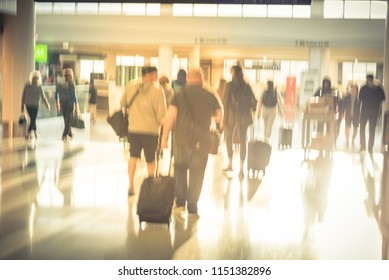 Vintage tone blurred busy group of people walking at airport with baggage in morning light. Abstract background passengers or tourist with luggage away at hallway terminal, back view