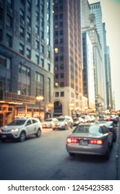 Vintage tone blurred busy street alley in downtown Chicago at sunset. Defocused bokeh light from long line of cars on street