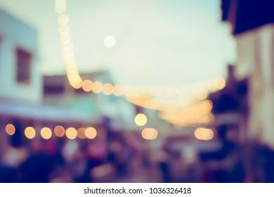 Vintage tone blurred defocused day of walking street festival in thailand bokeh background