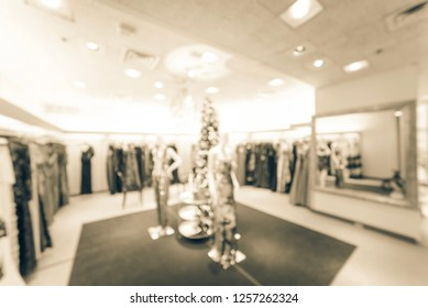 Vintage tone blurred image of upscale clothing boutique with mannequin wearing trending fashionable