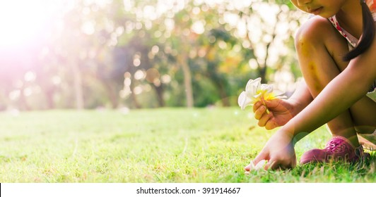 In vintage tone, girl pick flowers at the park in the evening.(Soft style for background)