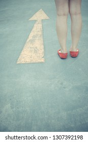 Vintage tone of Girl wear red shoes  walking towards with yellow traffic arrow signage on an asphalt road background