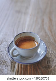 Vintage tone hot espresso one cup on wood background and coffee grander