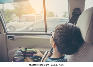 vintage tone image of Asian kid  sit on back seat in car and look to outside for background usage.
