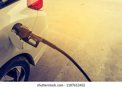 vintage tone image of gasoline nozzle in oil filling hole in gas station.