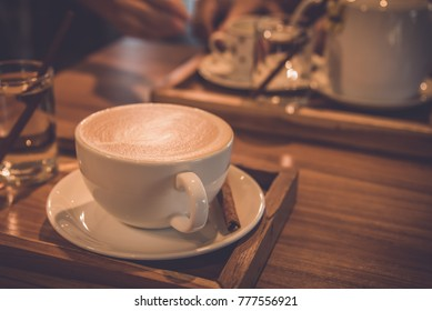 vintage tone image of glass coffee cup on table in cafe.