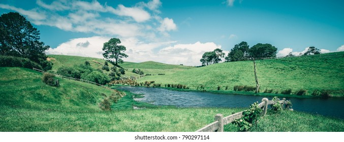 Vintage tone image of green grass field in the countryside landscape. Peaceful British rural area scenery. Beautiful hill agriculture farmland and pasture grassland in the country.
