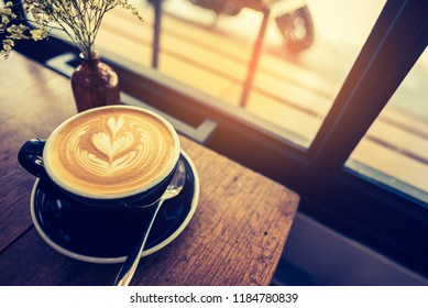 Vintage tone image of Latte coffee art in black cup on wooden table.