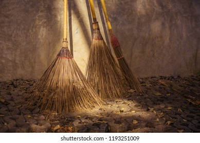 vintage tone image of old dirty coconut stick brooms on cement wall.