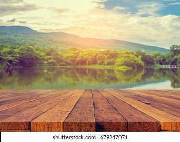 vintage tone image of old wooden table and the lake with rainy sky and mountain in background.