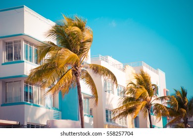 Vintage tone image of palm trees and typical retro art deco style buildings seen from South Beach Miami Florida