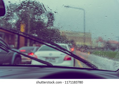 vintage tone image of people driving car on evening time with raindrop on glass and wiper  for background usage.(take photo from inside)