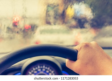 vintage tone image of people driving car on evening time with raindrop on glass  for background usage.(take photo from inside)
