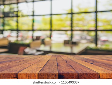 vintage tone image of selective focus on surface of wood table and blur restaurant for background usage.