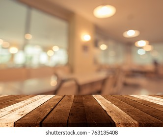 vintage tone image of selective focus on surface of wood table and blur restaurant for background usage .