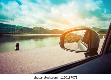 vintage tone image of wing mirror to see lake and mountain beside on day time for background.