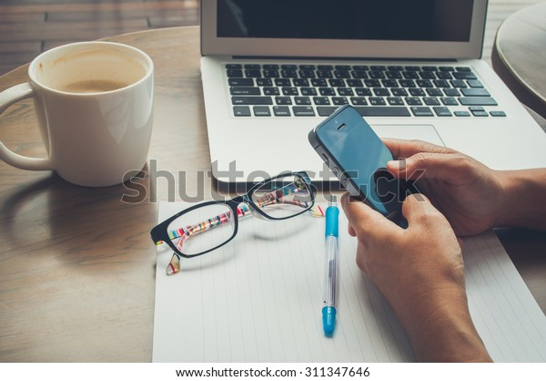 Vintage tone image for woman hold mobile phone on working time with coffee