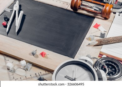 vintage tone image of wooden table top view of the chalk board with creative stationery items to draw, paint. For creative idea work of the artist.