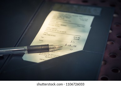 Vintage tone open leather bill holder restaurant check, pen. Soft focus receipt hand written total amount and tipping on outdoor picnic table, natural light. Paper invoice with suggested gratuities
