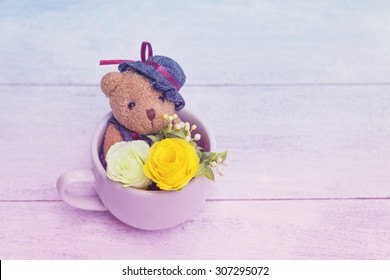 Vintage tone Teddy Bear sitting in coffee cup with flower