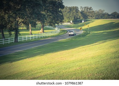 Vintage tone winding road, grassy lawn with white country style wooden fence. White fences on green lush oak trees at farm ranch land field in Louisiana, USA. Car driving through