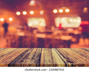 vintage tone wood table and  blur image of coffee shop or restaurant with bokeh on day time for background usage.