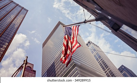 Vintage toned American flag and skyscrapers in Manhattan, New York City, USA.