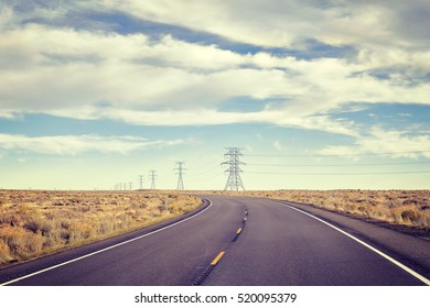 Vintage toned empty rural highway with electric poles.