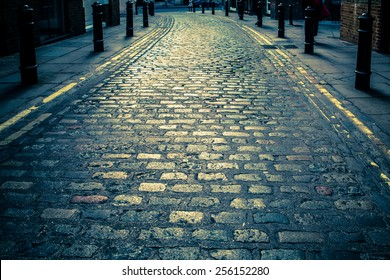 Vintage toned image of Old cobblestone road in London UK