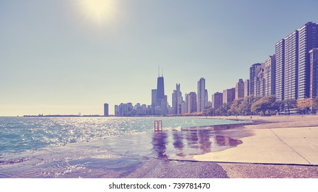 Vintage toned photo of Chicago city waterfront against the sun, USA.