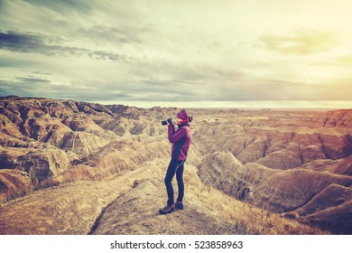 Vintage toned photo of a female photographer taking pictures at sunset, Badlands National Park, South Dakota, USA.