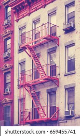 Vintage toned photo of a residential building fire escape in Manhattan, New York City, USA.
