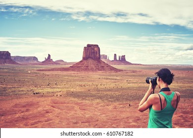 Vintage toned picture of female fit photographer takes pictures of buttes in the Monument Valley, USA.