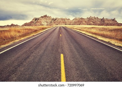 Vintage toned picturesque road in Badlands National Park, travel concept background, South Dakota, USA.