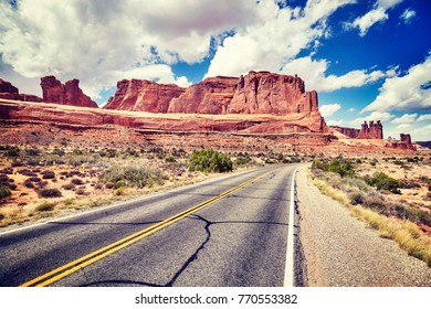 Vintage toned scenic road, travel concept picture, Arches National Park in Utah, USA.