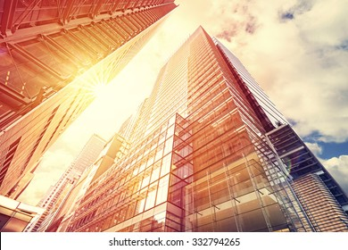Vintage toned sunset over skyscrapers, modern business background with flare effect.