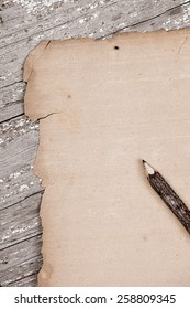 Vintage torn blank paper on rustic wooden table with bark covered pencil