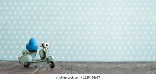 Vintage toy blue mototrcycle with blue heart on wooden table in nursery room