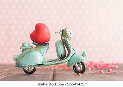 Vintage toy blue mototrcycle with red heart on wooden table in pink nursery room