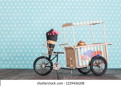 Vintage toy ice cream cart on wheels with bunch of flowers