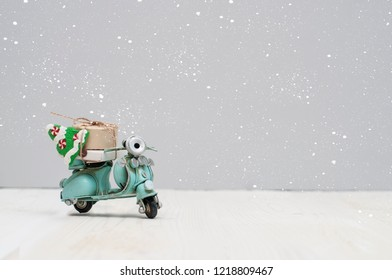 Vintage toy motorbike with christmas gifts and tree on grey background