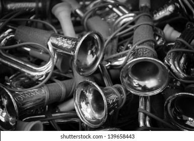 Vintage toy trumpets at flea market in France. Black and white.