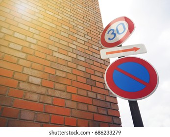 Vintage traffic sign post on the street and brick wall