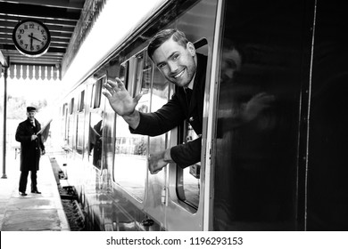 Vintage train arrives at railway station with handsome air force officer in uniform leaning out of window, laughing and waving