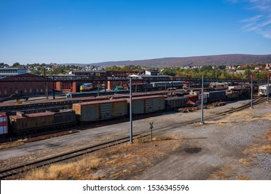Vintage train cars and locomotives, covered in rust and are in disrepair, rest on tracks in Scranton, PA, USA.