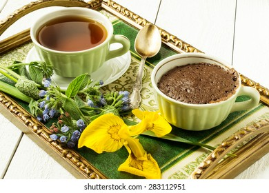 Vintage tray with Breakfast: delicious fresh cupcake in a cup of tea, a bouquet of flowers to set the mood. Selective focus